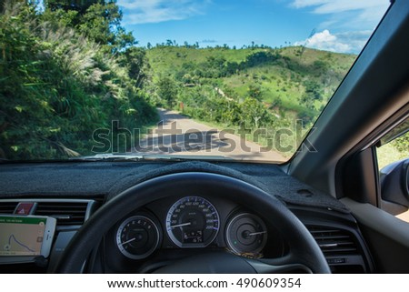 Car interior driving on road with forest
