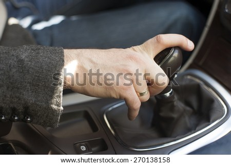 Car interior, elegant man, hand on a gear shift lever