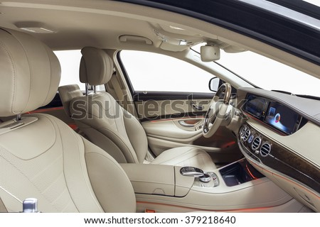 Car interior luxury. Interior of prestige modern car. Leather comfortable seats, dashboard & steering wheel. Beige cockpit with exclusive wood & metal decoration on isolated white background. - stock photo