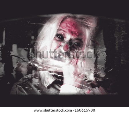 Car interior window view of a horror zombie eating the bones of a fast food attendant. Drive thru zombie apocalypse - stock photo