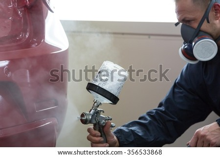 Car ist airbrushed with airgun by a body painter - stock photo