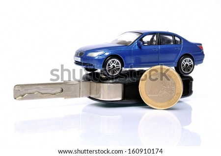 Car key and Euro coin with model car on top  - stock photo