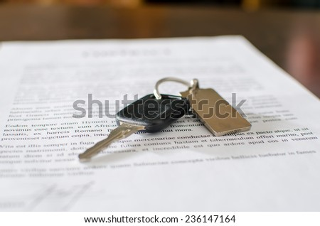 Car key on a signed sales contract, closeup - stock photo