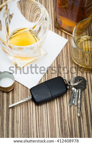 Car key on the bar with spilled alcohol - stock photo