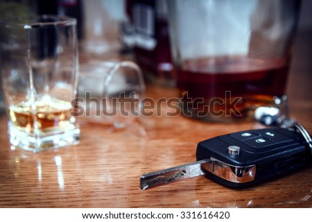 Car key on the bar with spilled alcohol and empty bottles. Booze driving concept. Drunk driver concept. in toning - stock photo
