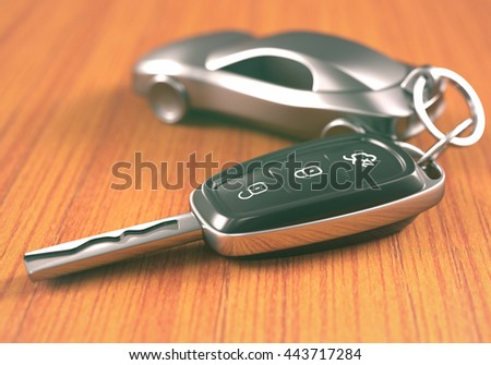 Car key with a car shaped keychain, on a wooden table. - stock photo