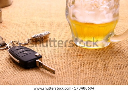 Car key with accident and beer mug, close up - stock photo