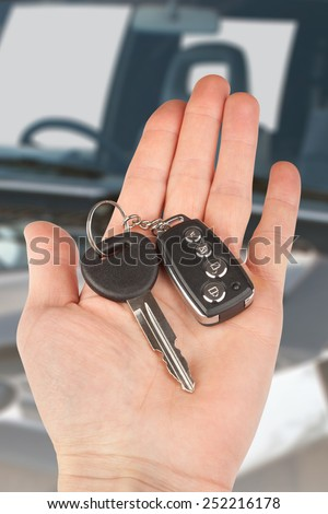 car key with alarm in hand over auto - stock photo