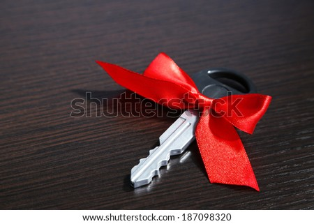 Car key with colorful bow on wooden background - stock photo