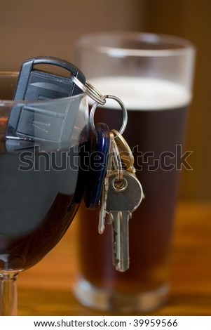 car keys in a glass of red wine shallow dof focus on the keys drink driving concept - stock photo