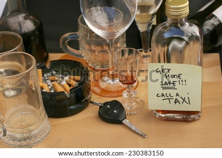Car keys on the table full of empty glasses, bottles and ashtray at party, don't drink and drive concept, post it note for taxi - stock photo