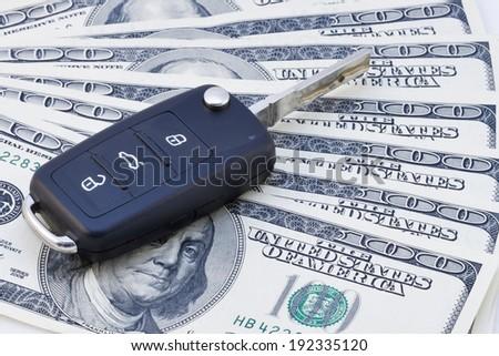 Car keys over the hundred dollar banknotes  - stock photo
