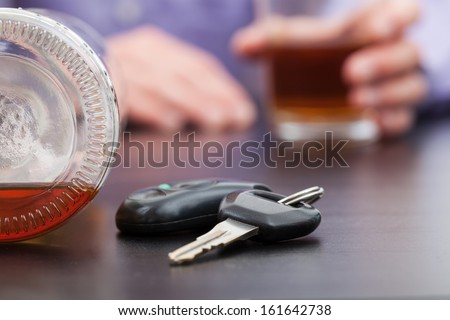 Car keys sittuated near the almost empty bottle of alcohol and the hands holding a filled glass