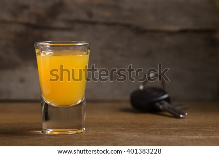 Car keys with one shot glasses over wood background - drink drive concept