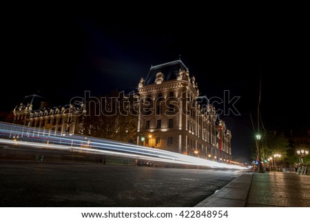 car light tracks at Paris at night in front of barracks justice palace near notre dame cathedral dome - stock photo