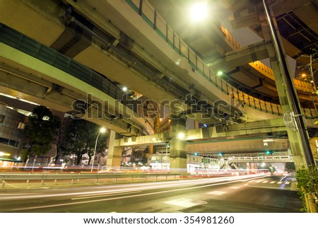 Car light trails and elevation angle of junction in Tokyo at night - stock photo