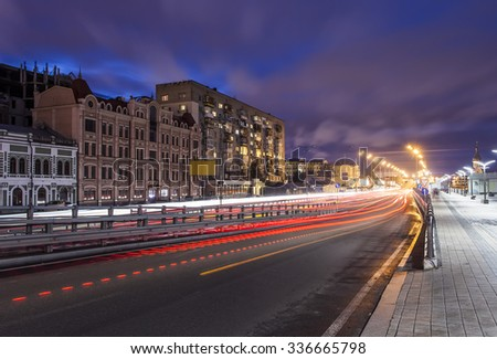 Car light trails and urban landscape. Moving car with blur light through city at night. Kiev city, Ukraine. - stock photo