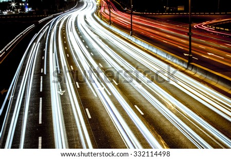 Car light trails at night highway - stock photo