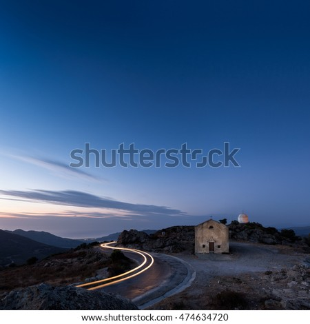 Car light trails curve around the mountain road past the San Sebastiano chapel and mausoleum near Palasca in the Balagne region of Corsica as dusk falls
