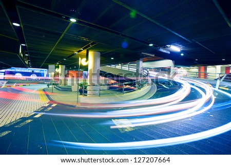 Car light trails in the parking lot - stock photo