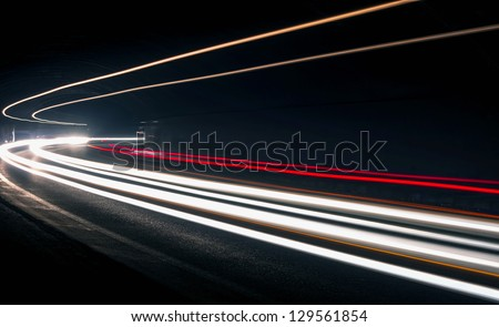 Car light trails in the tunnel. Art image . Long exposure photo taken in a tunnel - stock photo