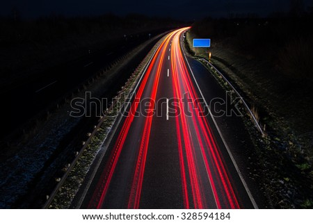 Car light trails with blue road sign, long exposure - stock photo