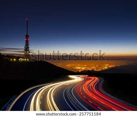 car lights at night towards the city and communications antenna - stock photo