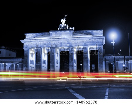 car lights at the brandenburger tor in berlin by night - stock photo