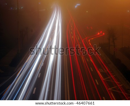 Car lights, busy night traffic and fog - stock photo