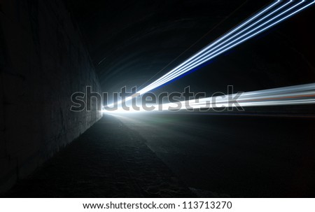 Car lights in a road tunnel in white and gray - stock photo