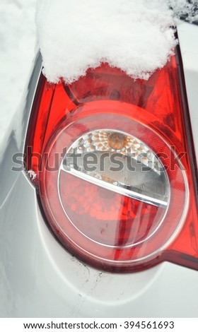 car lights in the snow.Tail light.Ice on the car light.Car under the snow