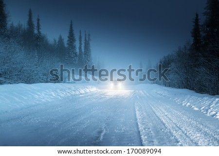 Car lights in winter Russian forest - stock photo