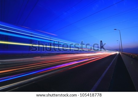 Car lights on a highway and transmission tower at night, long exposure photo of traffic - stock photo
