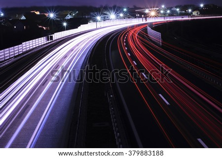 Car lights on a highway and transmission tower at night, long exposure photo of traffic