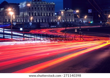Car lights on the central city streets at evening time - stock photo