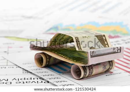 car made from dollar on chart background - stock photo
