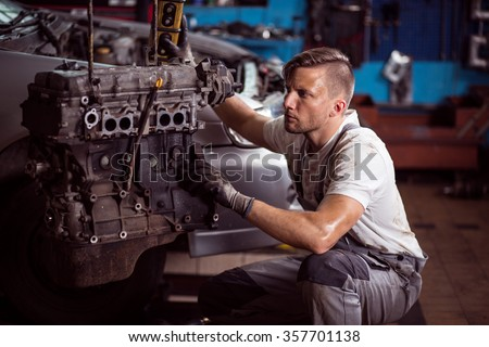 Car mechanic and car engine outside the vehicle - stock photo