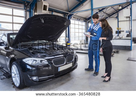 Car mechanic and customer stand next to the serviced car and looking through the checklist. The car had an annual checkup and stands in the garage with the hood open. - stock photo