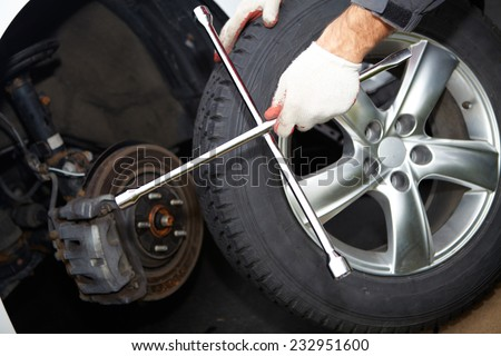 Car mechanic changing tire in professional car repair service
