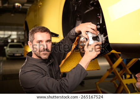 Car mechanic checking car at auto repair shop service station, brake pad and disc control - stock photo