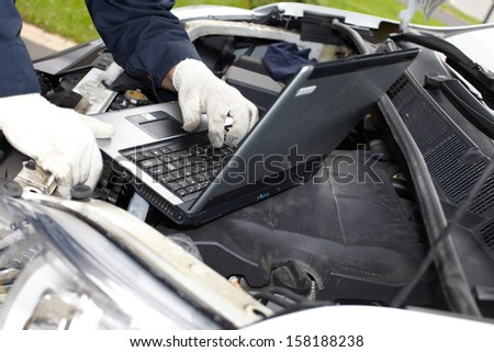 Car mechanic checking engine. Auto repair service. - stock photo