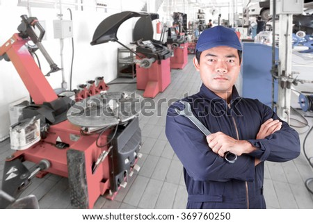 Car mechanic cross arm holding a wrench for maintaining car at the repair shop