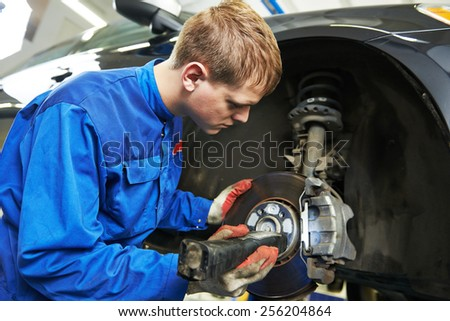 car mechanic examining car suspension of lifted automobile at repair service station - stock photo