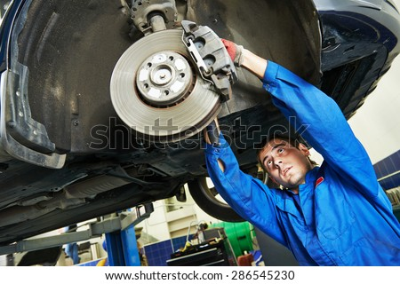 car mechanic examining car wheel brake disc and shoes of lifted automobile at repair service station - stock photo