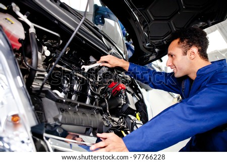Car mechanic fixing a broken engine at the garage - stock photo