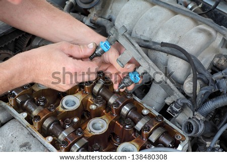 Car mechanic fixing fuel injector at  two camshaft gasoline engine - stock photo