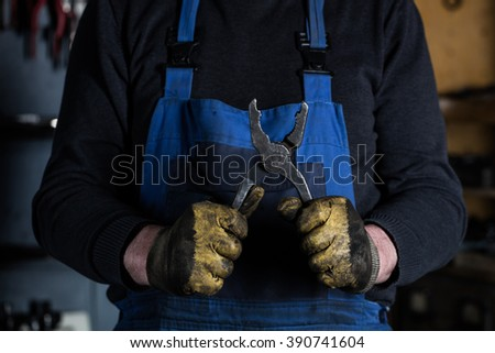 Car mechanic hands in garage with old gloves worker and rusty pliers.  Concept - stock photo