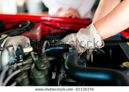 car mechanic in his repair shop standing next to the car - close-up of the engine - stock photo
