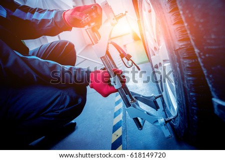 Car mechanic installing sensor during suspension adjustment. Wheel alignment work at repair service station