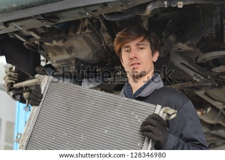 Car mechanic is Changing radiator - stock photo